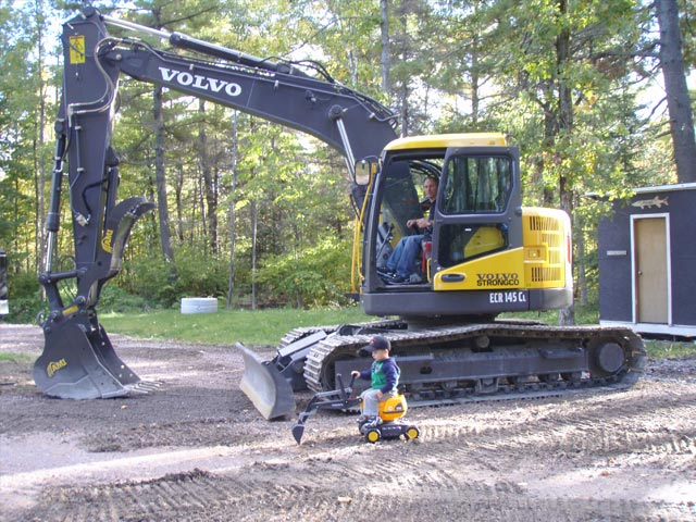 A Volvo digging machine next to a child on an imitation digging machine
